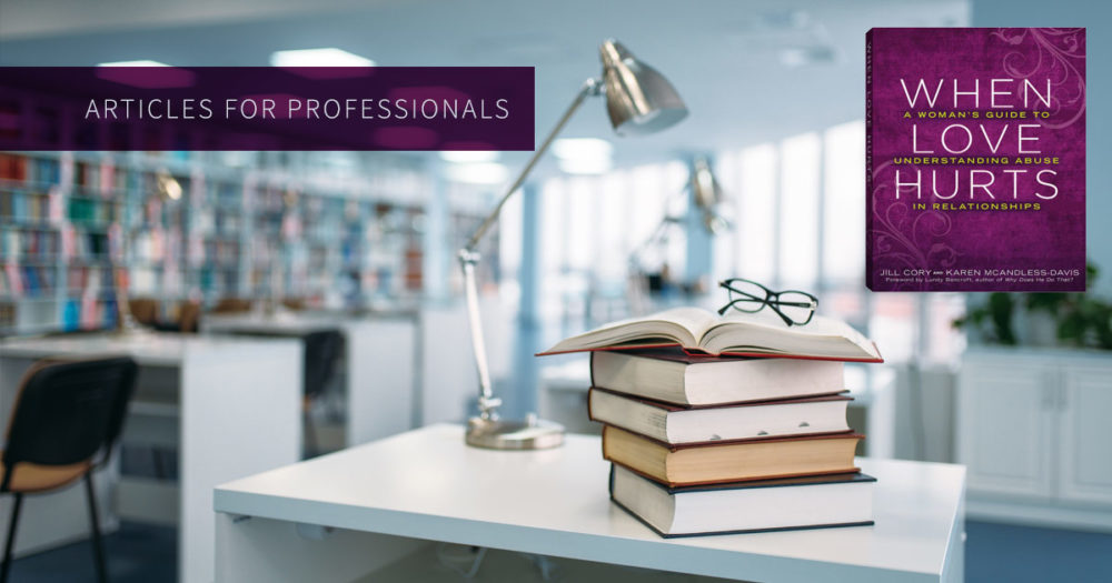 A stack of books sits on a table in a bright well lit library: Articles for professionals.