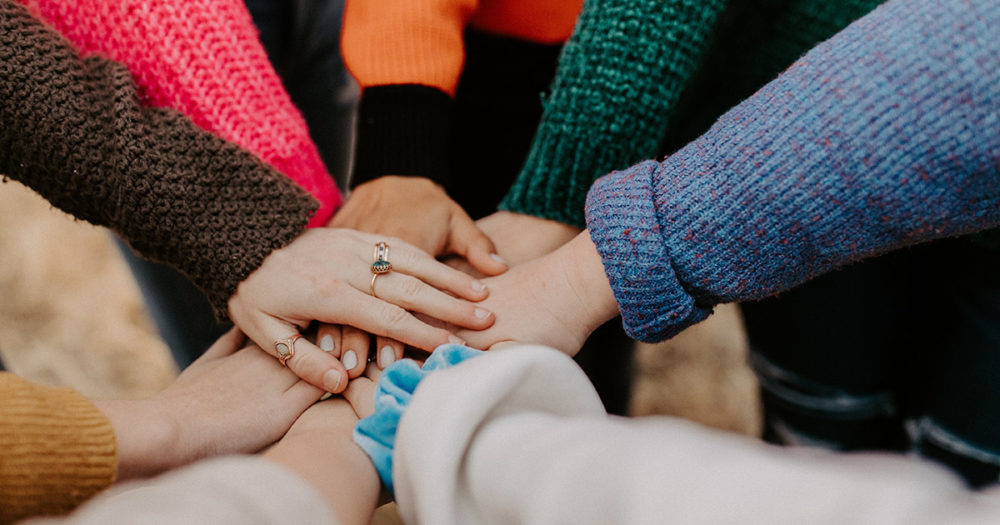 A circle of women lay their hands on top of each other in solidarity.