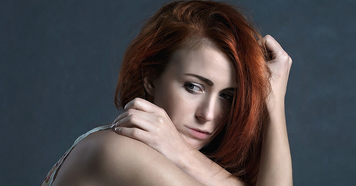 A red haired woman sits crouched down with one arm across her chest, resting on her shoulder, her other arm holding her head, a pensive expression on her face.