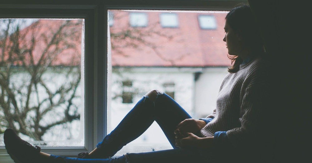 A woman sits in a window looking out.