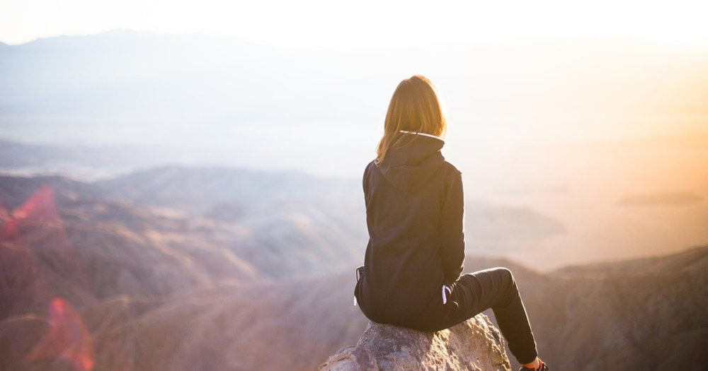 Looking out across a vast mountain vista, a woman sits high on a rock.
